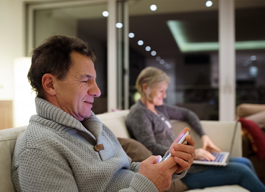 A couple relaxing with their computer and mobile phone