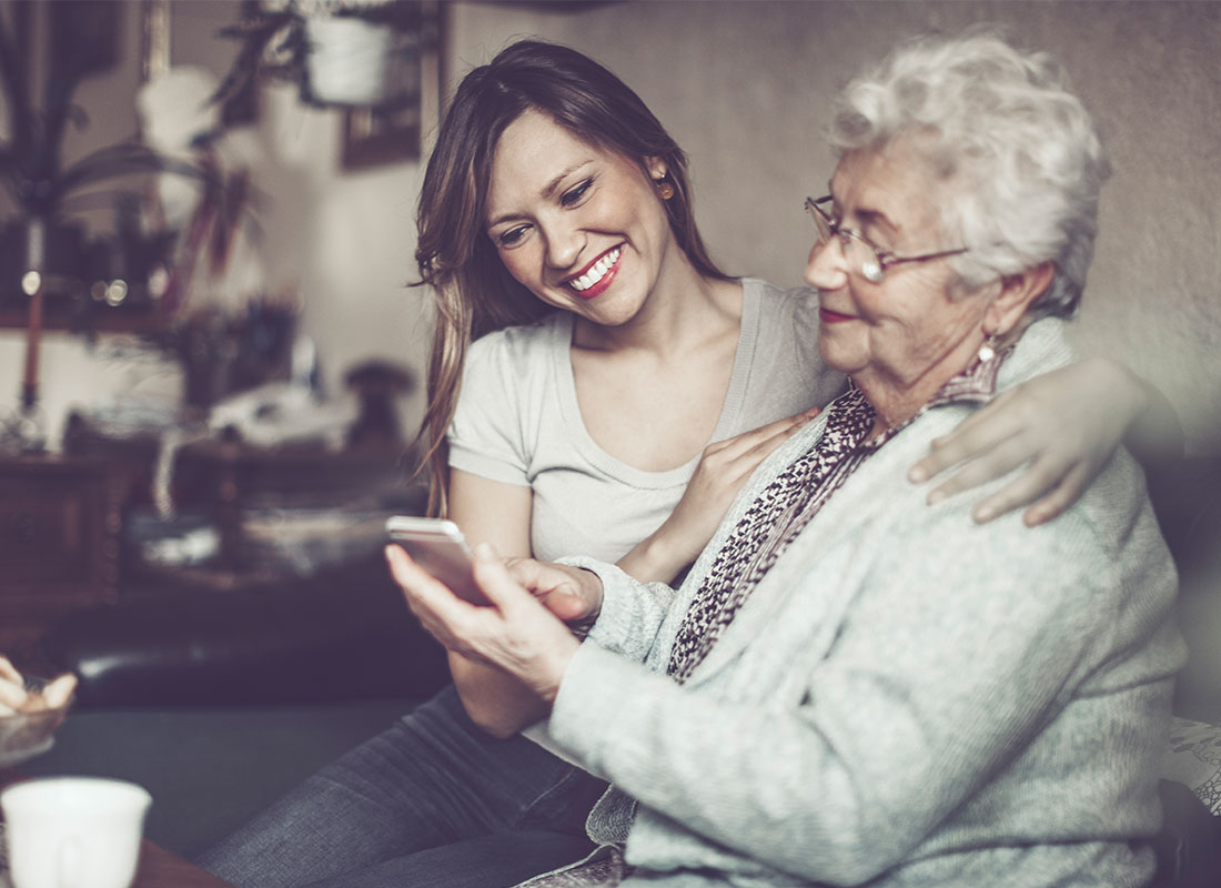 Mum and daughter sharing photos on a smartphone