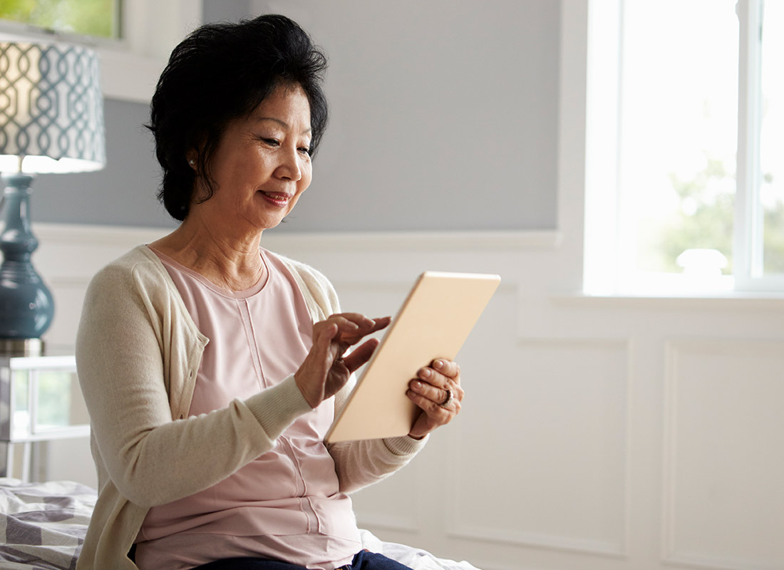 A lady catching up with her daughter using her tablet device