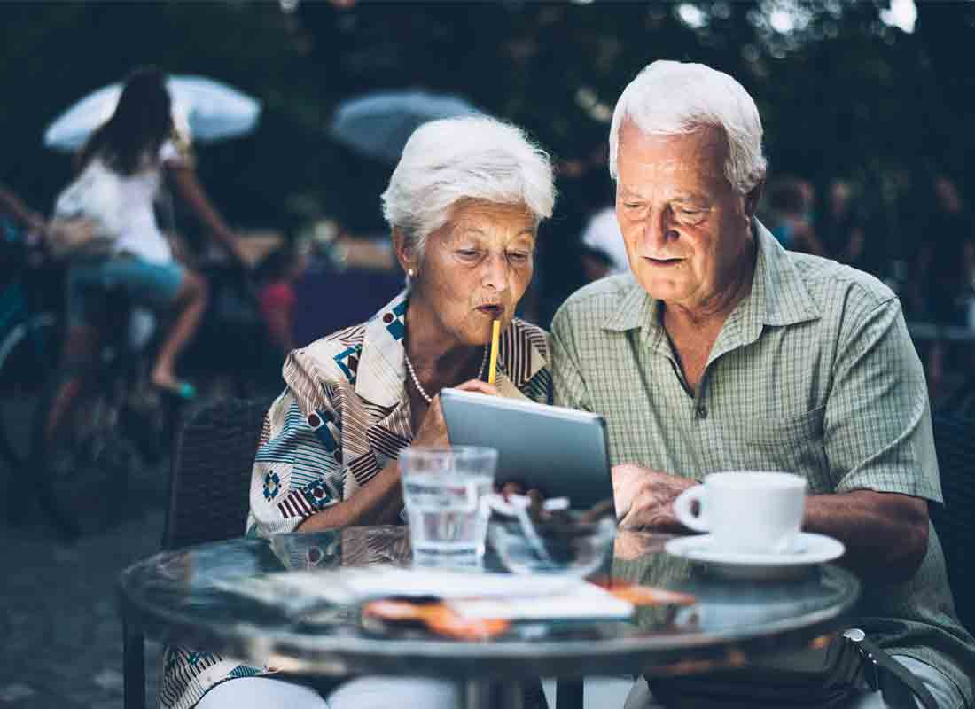 A holidaying couple enjoying a coffee and using their tablet device to catch up with family back home in Australia
