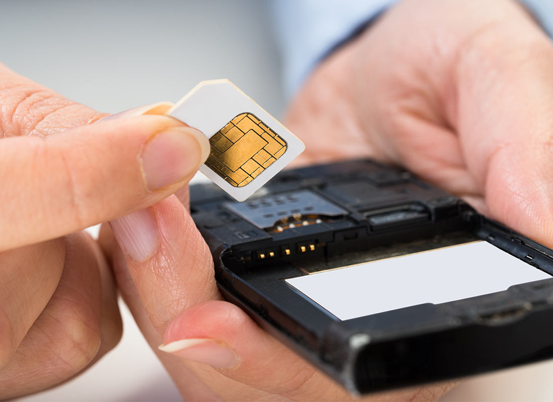 A new SIM card being inserted into a mobile phone