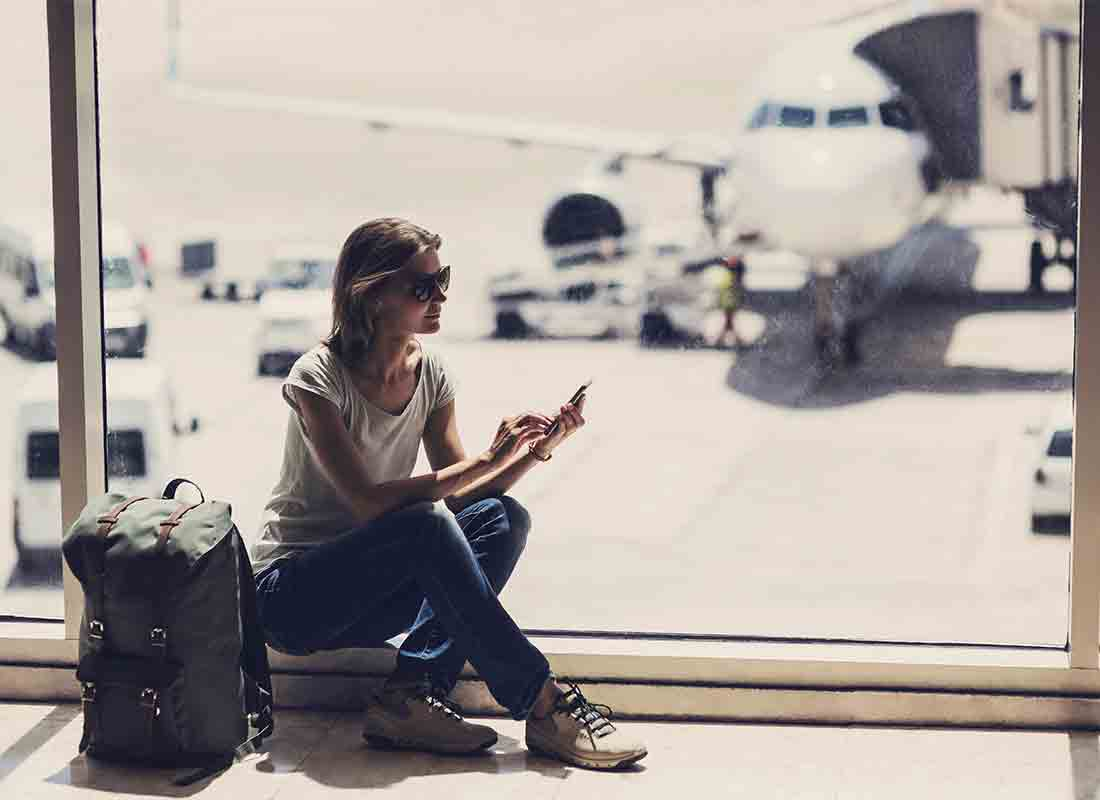 A passenger in an airport departure lounge switches her phone to Flight Mode