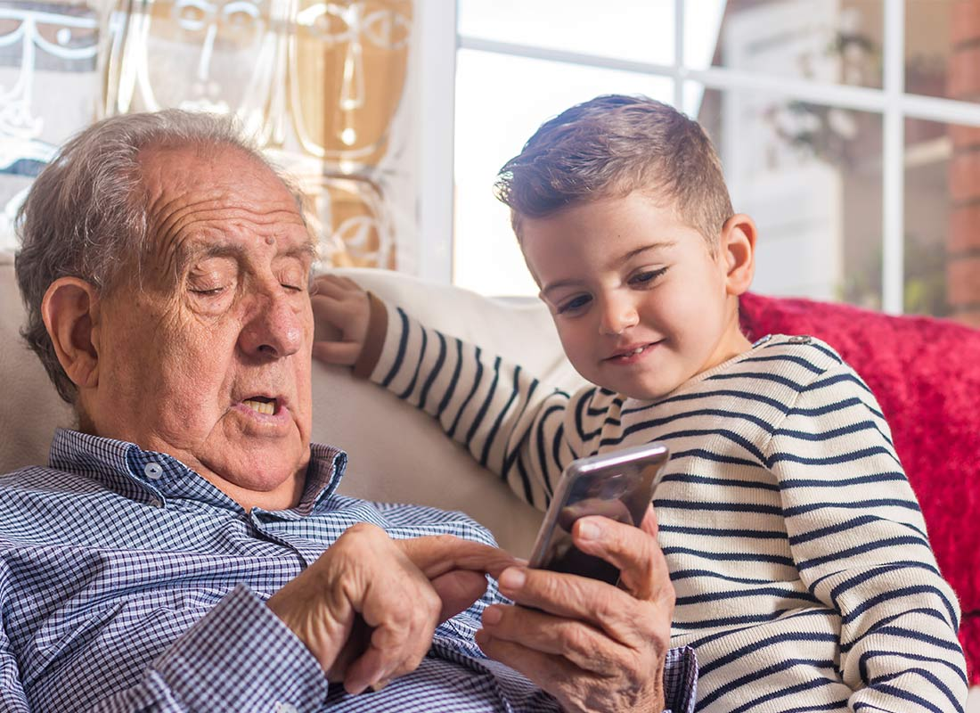 A grandfather and child enjoying using a mobile phone together
