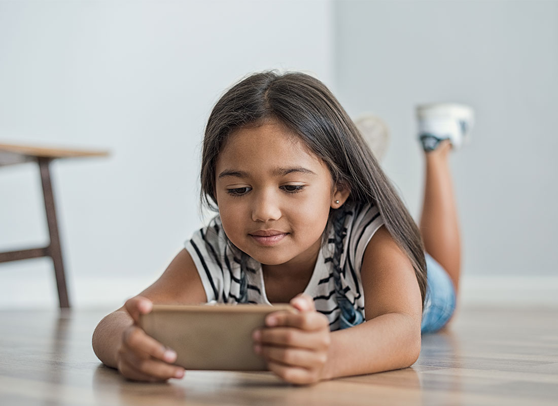 A young girl reading something on the internet on a smartphone at home.