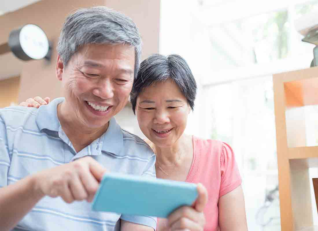 An older Asian couple laughing about something on the internet on a smartphone.