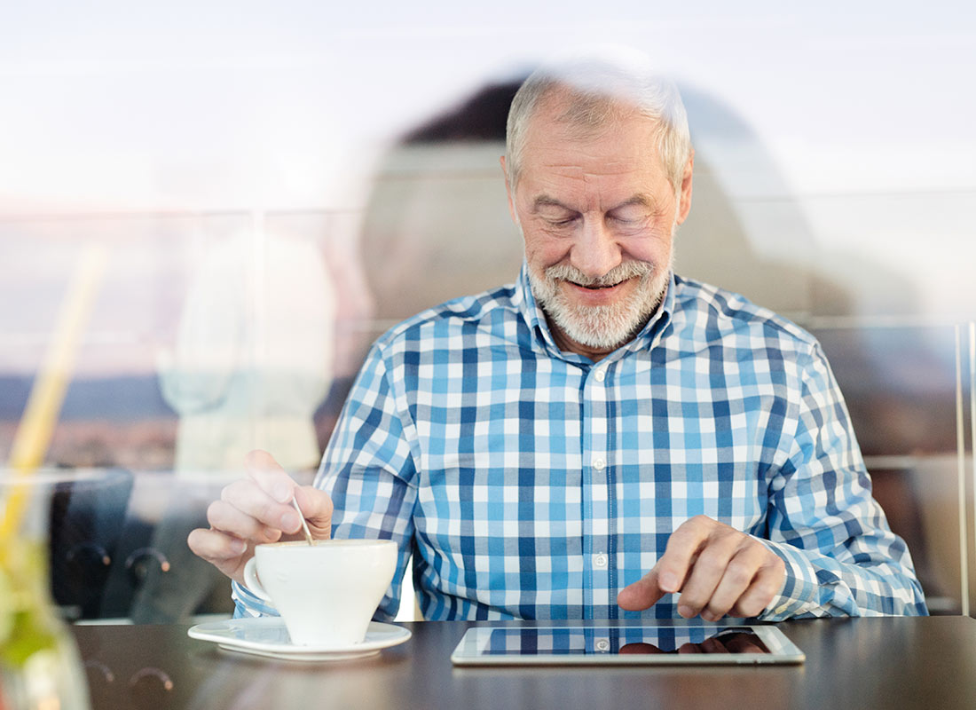A grandfather enjoying relaxing with a tablet device at a cafe