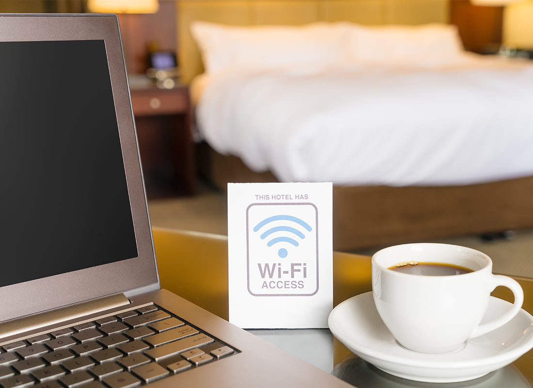 A hotel room with their Wi-Fi information card next to a cup of tea on the desk