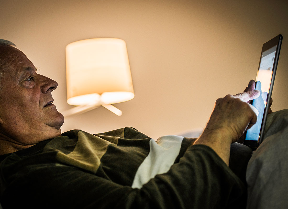 An older man relaxing on his sofa and reading the news on his tablet.