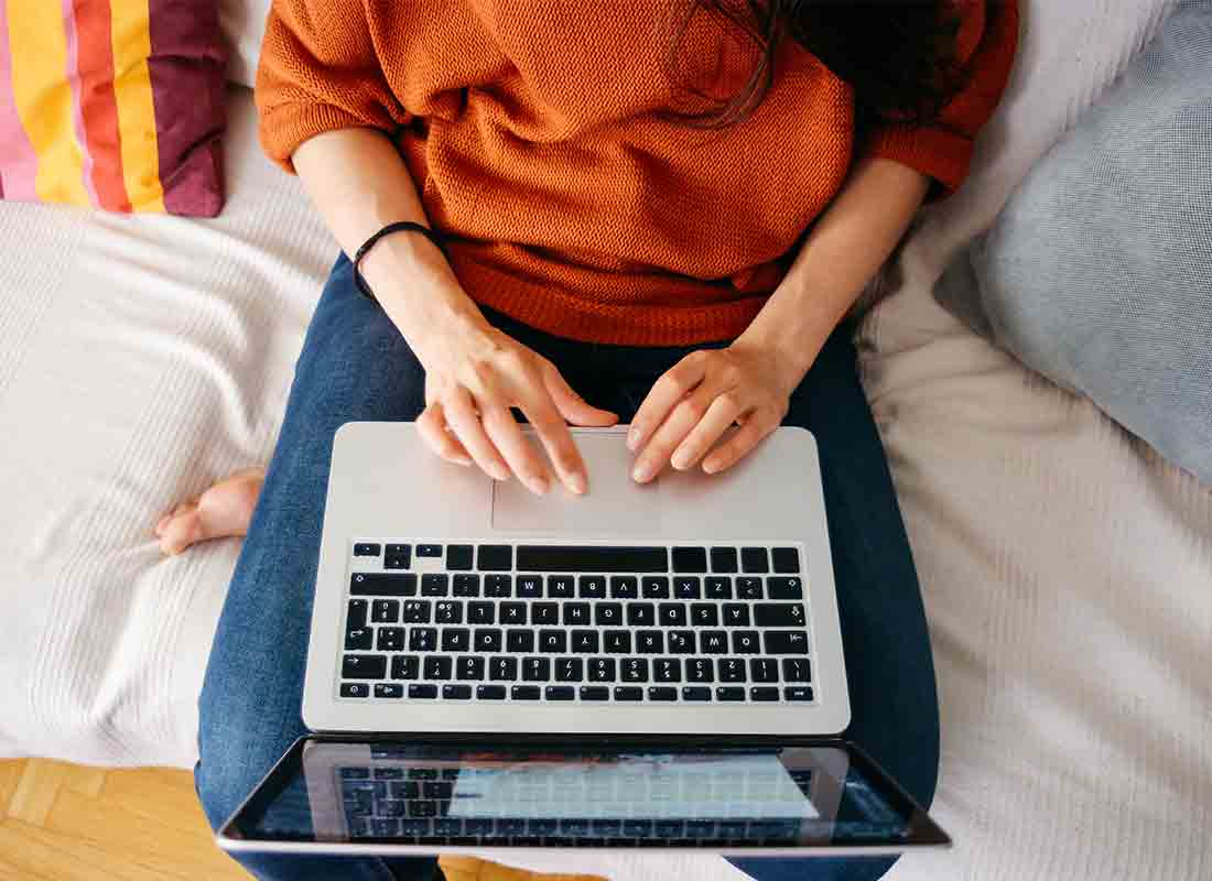 Top view of a woman working on her laptop using her home internet connection.