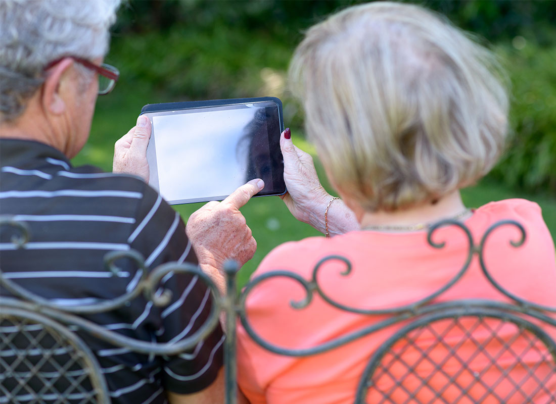 An older couple in the garden reading documents on their tablet using the home Wi-Fi network.
