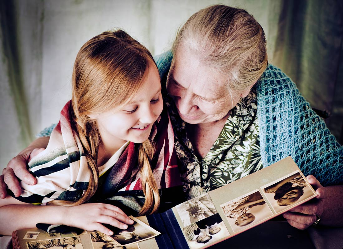 A great-grandmother and her great-granddaughter share precious moments looking at family photos