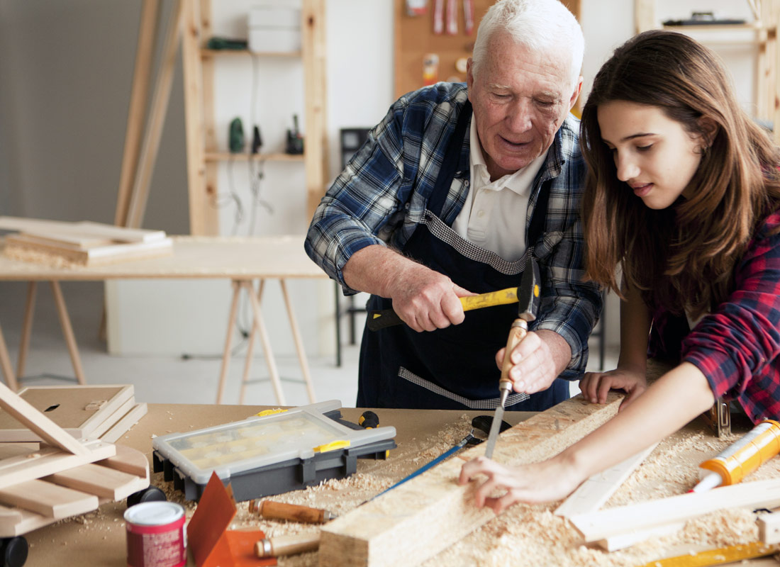 A grandfather explains how to use carpentry tools to his granddaughter