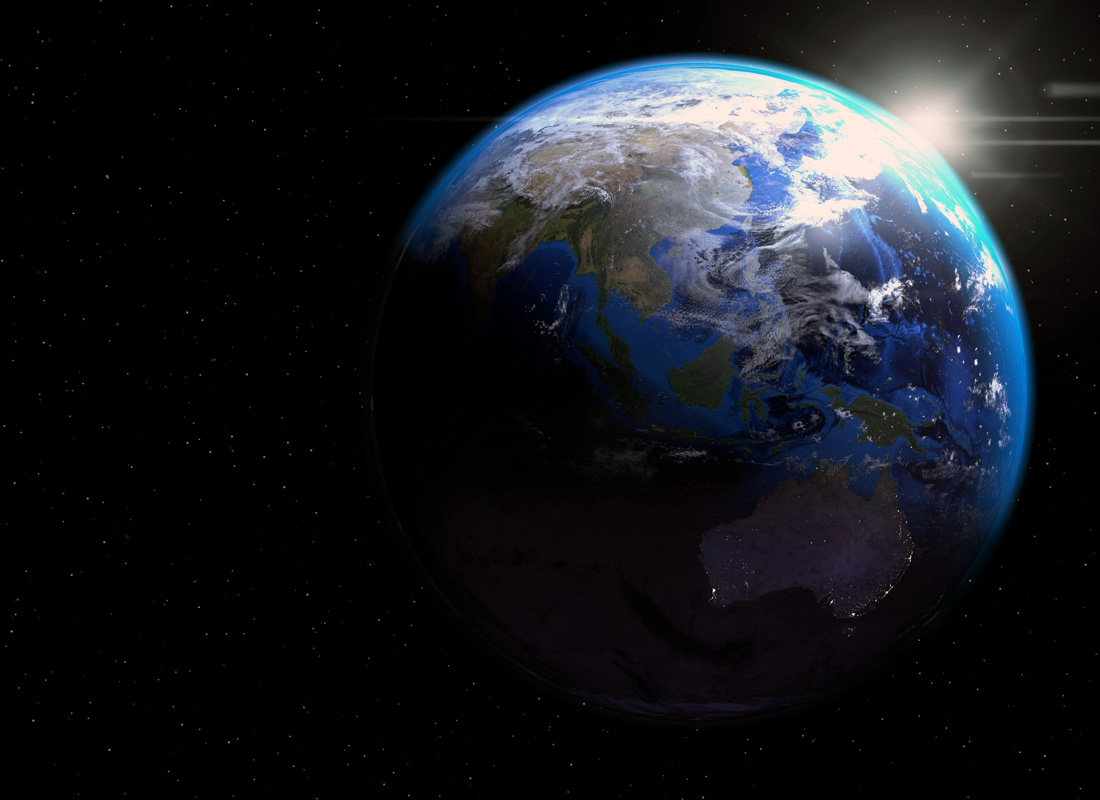 A photo of the Earth from space with sunlight glimpsing over its horizon.