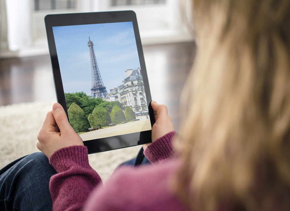 A photo of a woman holding a tablet with the Eiffel Tower in Paris pictured on it.