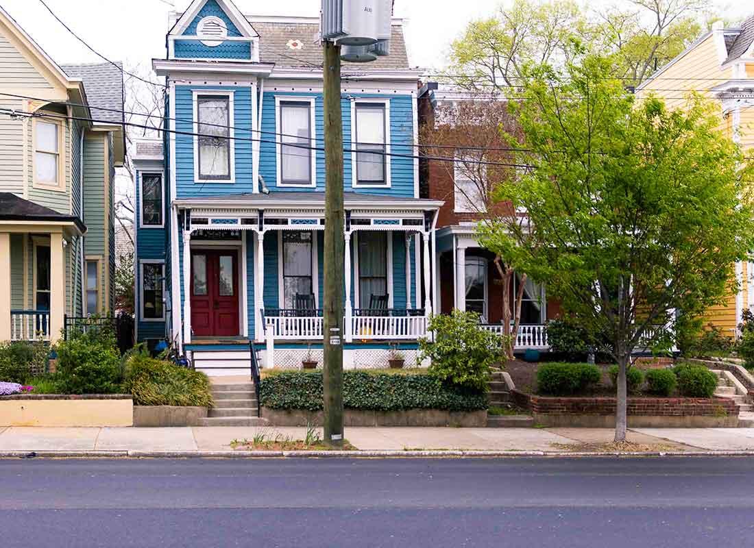 A colourful blue house on a street.
