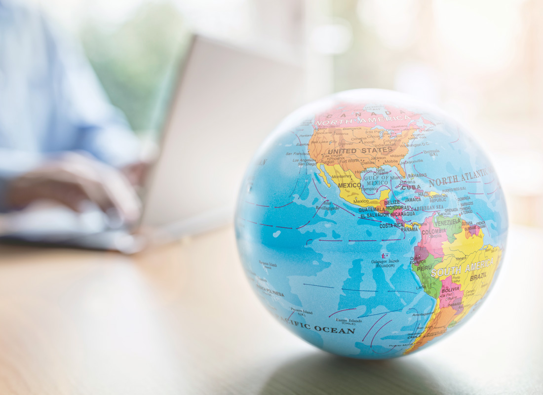A globe of the earth with a laptop computer in the background