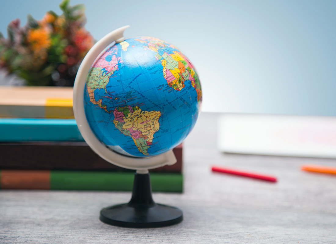 A small globe on a table with books and pencils in the background.