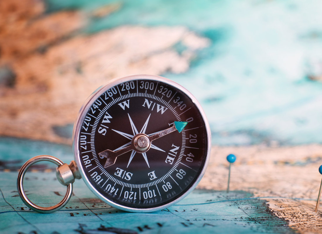 A photograph of a compass leaning on a map with some pins in it.