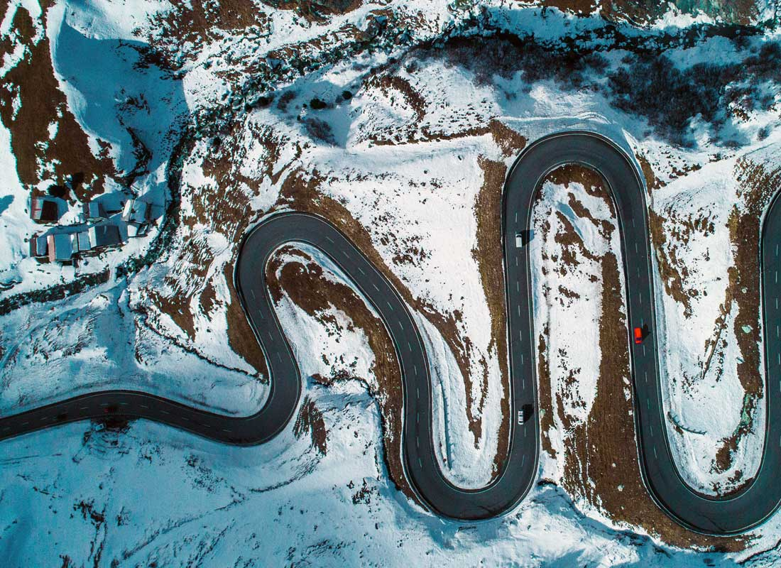 An aerial photograph of a winding road in a snowy winter landscape.